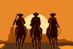 Cowboys riding horses in desert Stock Photo