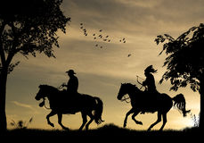 Cowboys Silhouette. Two Cowboys On Galloping Horses, designed on sunset/sunrise photo background Royalty Free Stock Photo