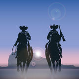 Cowboys silhouettes galloping across the prairie Royalty Free Stock Photos