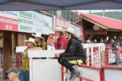 Cowboys sit on fence and watch race at the Williams Lake Stampede. Williams Lake, British Columbia/Canada - July 1, 2016: group of cowboys sit by the chutes Royalty Free Stock Image