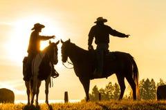 Cowboys sur des chevaux au lever de soleil, Colombie britannique, Canada photographie stock libre de droits