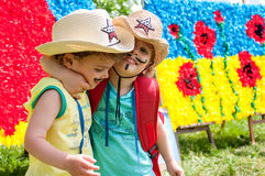 Cowboys with Ukrainian background. Three year old identical twins hugging each other. The picture on the background contains the Ukrainian flag and poppies, the Stock Image
