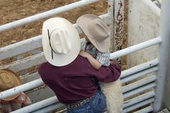 Cowboys, young and old. Cowboy father and son watching rodeo action Royalty Free Stock Photography