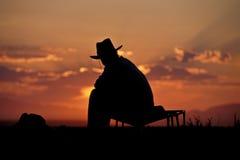 Cowboyschattenbild gegen Sonnenaufgang Stockbild