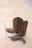 Cowboystiefel u. Gewehr auf Steinplatte Stockfotografie