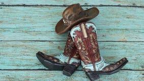 Cowboystiefel und Hut auf einem Knickentenhintergrund lizenzfreies stockfoto