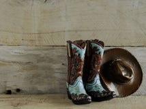 Cowboystiefel und Hut auf hölzernem Hintergrund lizenzfreie stockfotos