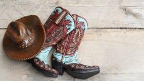 Cowboystiefel und Hut auf hölzernem Hintergrund stockbilder