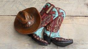 Cowboystiefel und Hut auf hölzernem Hintergrund lizenzfreies stockfoto
