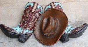 Cowboystiefel und Hut auf hölzernem Hintergrund lizenzfreies stockbild