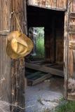 Cowboystrohhut und geöffnete Türen des alten Stalles Stockfotografie