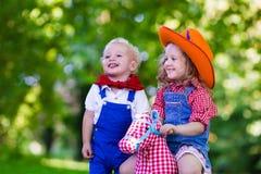 Cowboyungar som spelar med leksakhästen Arkivbilder
