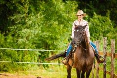 Cowgirl που κάνει την ιππασία στο λιβάδι επαρχίας Στοκ Εικόνες