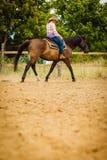 Cowgirl που κάνει την ιππασία στο λιβάδι επαρχίας Στοκ Εικόνα