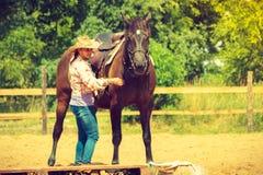 Cowgirl που παίρνει το άλογο έτοιμο για το γύρο στην επαρχία Στοκ φωτογραφία με δικαίωμα ελεύθερης χρήσης