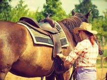 Cowgirl που παίρνει το άλογο έτοιμο για το γύρο στην επαρχία Στοκ φωτογραφίες με δικαίωμα ελεύθερης χρήσης
