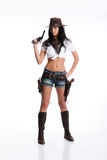 Cowgirl. Young woman dressed in Western style on isolated background with two revolvers Royalty Free Stock Photos