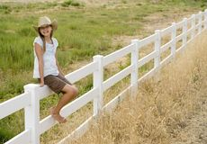 Cowgirl. Cute little cowgirl sitting on a white picket fence Stock Image