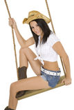 Sexy and beautiful Caucasian cowgirl playing on a wooden swing Royalty Free Stock Photos