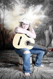 Cowgirl with acoustic guitar Stock Image