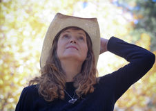 A Cowgirl with Autumn Leaves Behind Her Stock Images