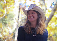 A Cowgirl with Autumn Leaves Behind Her Stock Photo