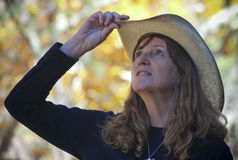 A Cowgirl with Autumn Leaves Behind Her Royalty Free Stock Photos