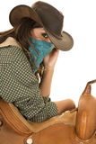 Cowgirl with bandana on face lean on saddle Royalty Free Stock Photography