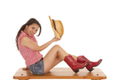 Cowgirl benchholding hat in hand Royalty Free Stock Photo