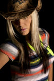 Cowgirl on a black background colorful shirt eyes hidden. A cowgirl wearing her western hat, with her eyes hidden Stock Images
