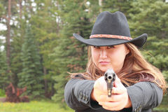 Cowgirl in Black Girl Shooting Revolver in Rain. Photo of a pretty cowgirl in black cowboy hat shooting a revolver while it is raining Stock Image