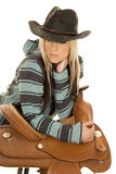 Cowgirl in blue and black poncho lean on saddle look down Royalty Free Stock Photos