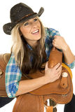 Cowgirl blue shirt black hat lean on saddle smiel looking up Stock Images