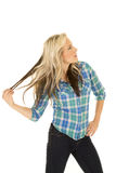 Cowgirl blue shirt pull hair Royalty Free Stock Image