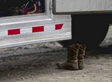 Cowgirl Boots. Empty cowboy boots next to the runner of a horse trailer stock image
