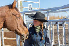 Cowgirl and a brown horse. Close-up of a cowgirl and her horse Stock Photography