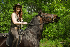 Cowgirl on brown horse Stock Images