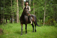Cowgirl on brown horse Stock Image