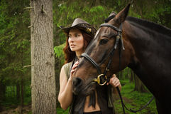 Cowgirl with brown horse. Young cowgirl with brown horse in the forest Royalty Free Stock Photos