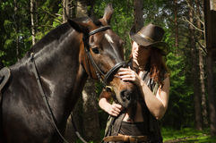 Cowgirl and brown horse. Young cowgirl with brown horse in the forest Stock Image
