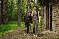 Cowgirl with brown horse Royalty Free Stock Photo