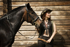 Cowgirl and brown horse Stock Photos