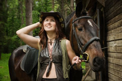 Cowgirl with brown horse Stock Image