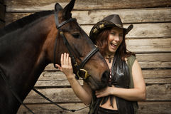 Cowgirl and brown horse Stock Photo