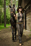 Cowgirl and brown horse Stock Images
