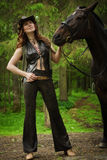 Cowgirl with brown horse. Young cowgirl with the brown horse on a ranch Stock Photos