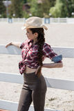 Cowgirl in checkered shirts and hat leaning on fence and looking away Stock Photography
