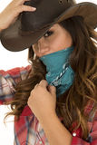 Cowgirl close hand on hat and bandana over face looking stock photography