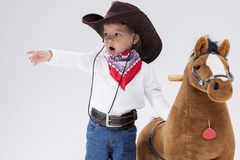 Cowgirl Clothing Posing With Symbolic Plush Horse. Little Children Concepts. Caucasian Girl in Cowgirl Clothing Posing With Symbolic Plush Horse Against White Stock Photography