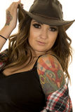Cowgirl with colorful tattoos hold hat look close. A woman in her western hat, with her plaid shirt off of her shoulder, showing off her tattoo stock image